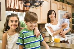 Family in kitchen. Hispanic mother and children smiling at viewer in kitchen Stock Image