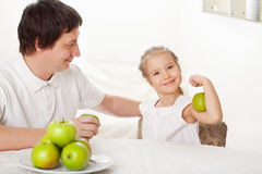 Family in the kitchen with apple Royalty Free Stock Photos