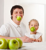 Family in the kitchen with apple Stock Images