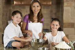 Family In Kitchen Cooking & Baking. An smiling mother, daughter and son family cooking and baking chocolate chip cookies in a kitchen at home Royalty Free Stock Image