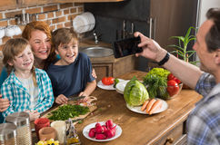 Family In Kitchen Cooking Food Father Taking Photo On Cell Smart Phone Of Mother Son And Daughter Sitting At Table. Preparing Healthy Meal Stock Photo
