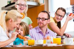 Family in kitchen having breakfast together stock photo