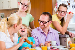 Family in kitchen having breakfast together Stock Photos