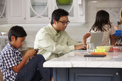 Family In Kitchen Having Breakfast And Using Digital Devices Stock Photo