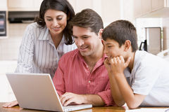 Family in kitchen with laptop smiling Royalty Free Stock Photo