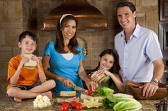 Family In Kitchen Making Healthy Sandwiches. An attractive happy, smiling family of mother, father, son and daughter making healthy sandwiches with ham, cheese stock photography