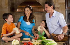 Family In Kitchen Making Healthy Sandwiches. An attractive happy, smiling family of mother, father, son and daughter making healthy sandwiches with ham, cheese royalty free stock photo