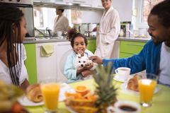 Family in kitchen in the morning having breakfast stock photography