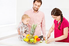 Family in kitchen. Mother is preparing fruit for child in the kitchen Stock Photo