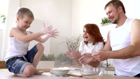The family in kitchen plays scattering flour for cooking,slow mo. On this video you can see as parents with the son knead dough in a transparent bowl. A close stock footage