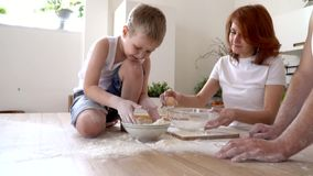The family in kitchen plays scattering flour for cooking, slow motion. On this video you can see as parents with the son knead dough in a transparent bowl. A stock video