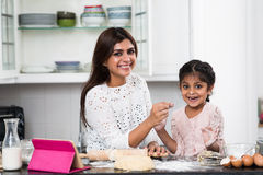 Family in kitchen. Portrait of cheerful mother and her kid in kitchen Stock Image