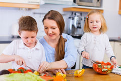 Family at kitchen. Young mother and her two kids making vegetable salad Stock Photo