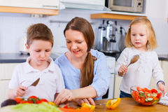 Family at kitchen. Young mother and her two kids making vegetable salad Stock Image