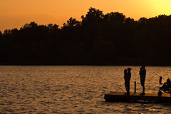 Family on lake. A couple with kids on a lake sunset Royalty Free Stock Photography