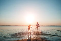 Family on the lake against a beautiful sunset. A happy life, happiness, family vacations. stock image