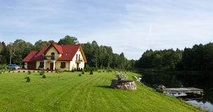 Family lake house. The family house on the lake, with a garden and a bridge Royalty Free Stock Photography