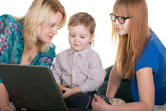 Family at the laptop. Mom explains her choldren how to use a laptop; isolated on the white background Stock Images