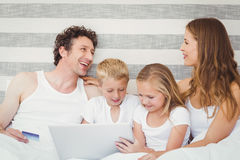 Family with laptop on bed Stock Photography