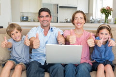 Family with laptop gesturing thumbs up on sofa Royalty Free Stock Images