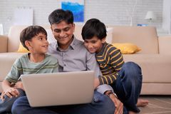 Family with laptop. Happy Indian family watching something on laptop at home Stock Photo