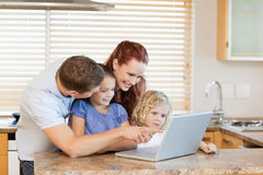 Family with laptop in the kitchen Stock Image
