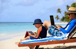 Family with laptop and touch pad on beach Stock Photo