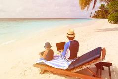 Family with laptop and touch pad on beach Royalty Free Stock Photos