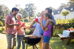Family laughing and talking while preparing barbecue in the park Stock Photography