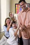 Family laughing together at home, mom teasing son Stock Photos
