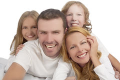 Family laughing together while laying on bed covered with white Stock Photos