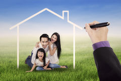 Family laughing under a dream home Royalty Free Stock Photos