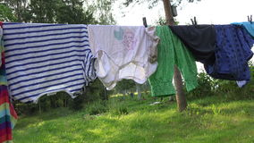 Family laundry colorful clothes  in farm on string stock video footage