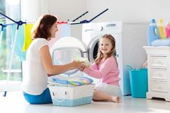 Family in laundry room with washing machine Stock Photo