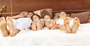 Family laying in bed with feet forward Royalty Free Stock Photos