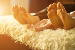 Family laying on bed, their feets on focus. Mother, father and newborn baby son Stock Photo