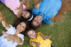 Family Laying Down Hands Up Laughing Royalty Free Stock Images