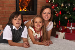 Family laying by the fire on Christmas eve Stock Images