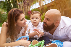 Family laying in park. Hispanic family laying in park with small son sunny day light Royalty Free Stock Photos