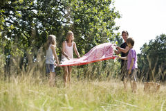 A family laying a picnic blanket on the grass Stock Photos