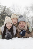 Family laying in snow for portrait Stock Photography