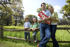 Family leaning on rural fence and holding ?sold? sign Royalty Free Stock Photos
