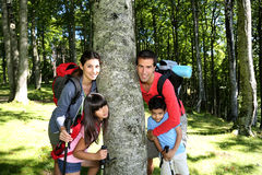 Family leaning on the tree in forest Royalty Free Stock Photography