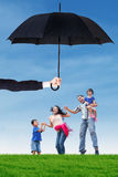 Family leap on the meadow under umbrella. Image of cheerful family enjoy holiday and jumping together at field under umbrella. Life and family insurance concept Royalty Free Stock Photo