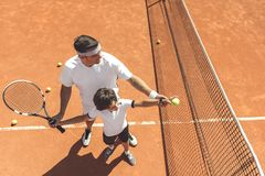 Family learning to play tennis Royalty Free Stock Photo