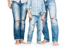Family legs in tattered jeans royalty free stock image