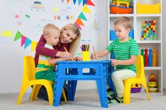 Children with mom and draw pictures in the kids room. Family leisure.Children with mom and draw pictures in the kids room stock photos