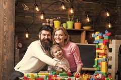 Family leisure concept. Parents hugs, watching son playing, enjoy parenthood. Kid with parents play with plastic blocks. Build construction. Father, mother and stock photography
