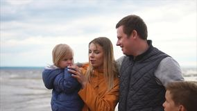 Family leisure. Family of four standing on a beach at cold windy weather stock video footage