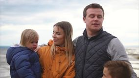 Family leisure. Family of four standing on a beach at cold windy weather stock video